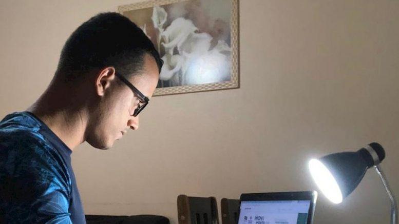Homem vestido com camiseta do Movimento Paralímpico trabalha em frente a um computador