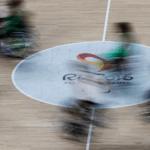 Lance do jogo entre Brasil e Canadá, pelo basquete em cadeira de rodas nos Jogos do Rio 2016. Cinco atletas disputam jogada com a cadeira de rodas em movimento no centro da quadra.