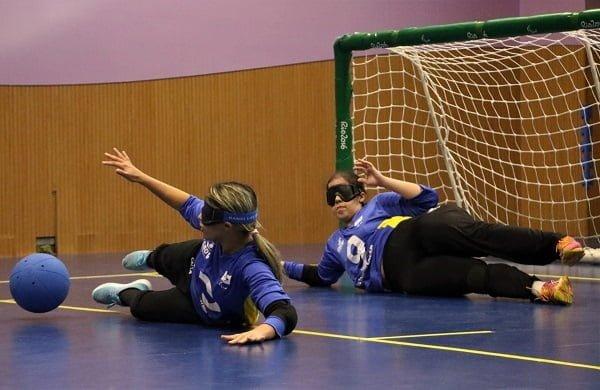 Larissa se estica para defender a bola com as pernas. Atrás dela, Victoria Amorim está caída para o lado direito fechando este ângulo do gol defendido.
