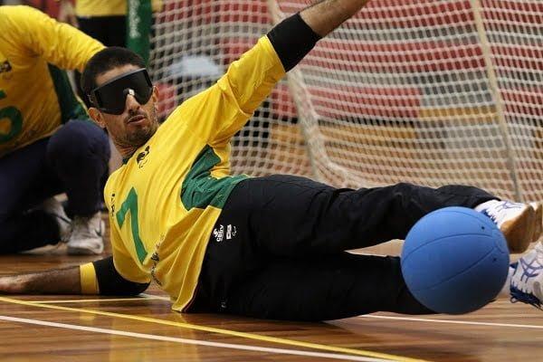 Deitado com o apoio no lado direito do corpo, Emerson faz a defesa com as pernas, a bola está totalmente encostada em seus pés