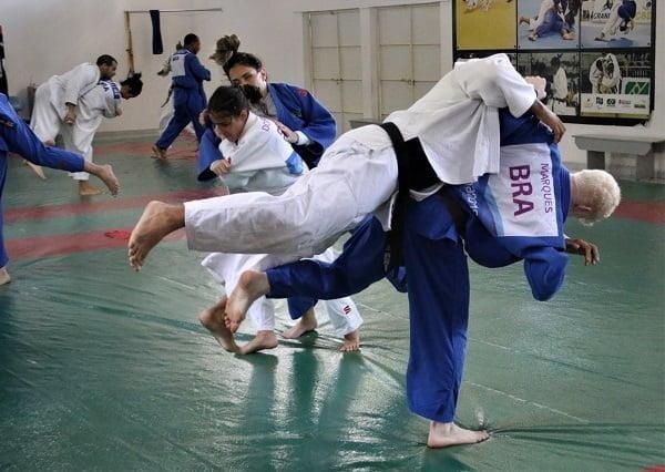 vários atletas fazem exercícios de golpe lado a lado. Em primeiro plano, Thiego Marques gira o corpo para derrubar seu oponente