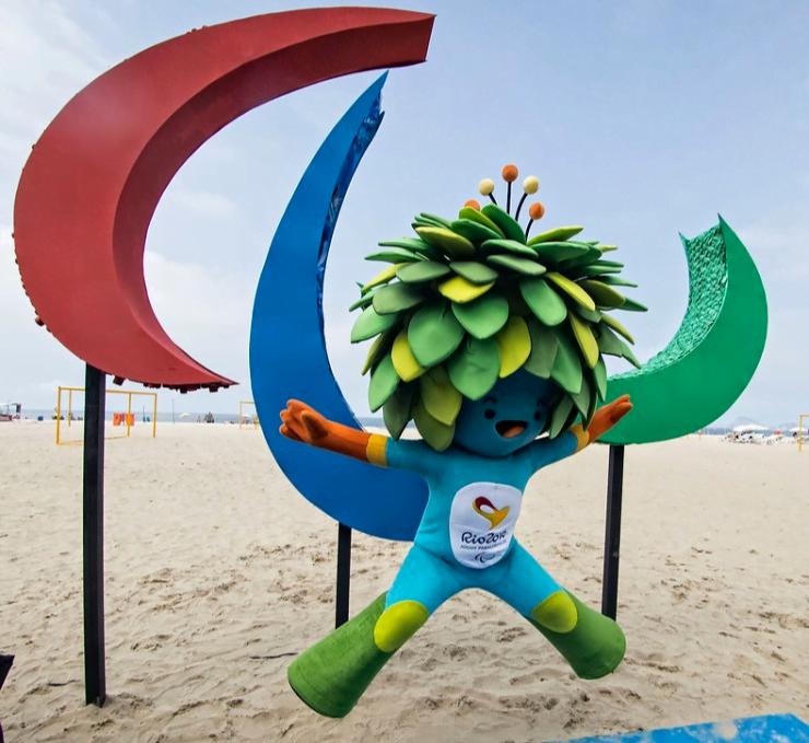 A mascote Tom salta em frente ao símbolo dos Agitos na praia da Copacabana, no Rio de Janeiro, em 2016