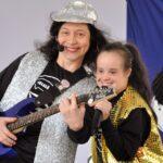 celelê tocando guitarra no palco ao lado de uma criança, elas usam roupas pretas com coletes brilhantes
