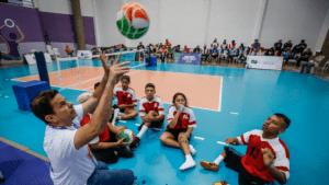 Professor ensina gesto do vôlei sentado para crianças com deficiência no CT Paralímpico em 2018.