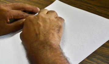 Homem lê em braille