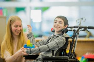 mulher brinca com criança em cadeira de rodas