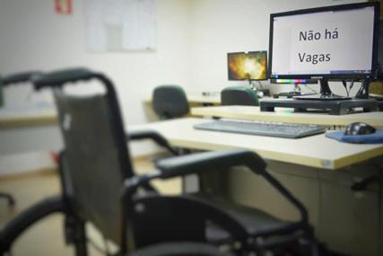"""Cadeira de rodas vazia em frente ao PC escrito """"Não há Vagas"""""""