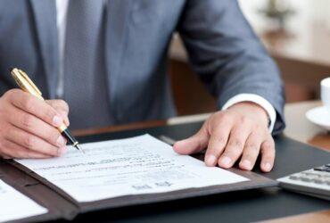 homem assinando papel