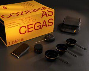 instrumentos de cozinha pretos e sua embalagem amarela escrito Cozinha às Cegas