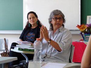 foto de mulher grisalha fazendo palestra sendo observada por uma outra pessoa (mulher) que a ouve atentamente. Estão dentro de uma sala de aula.