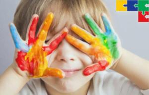 Ilustração de criança autista com mãos cheias de tinta colorida em frente ao rosto, tampando os olhos