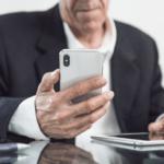 senhor segura celular na mão