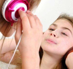 garota branca em frente ao espelho com headphones ouvindo música