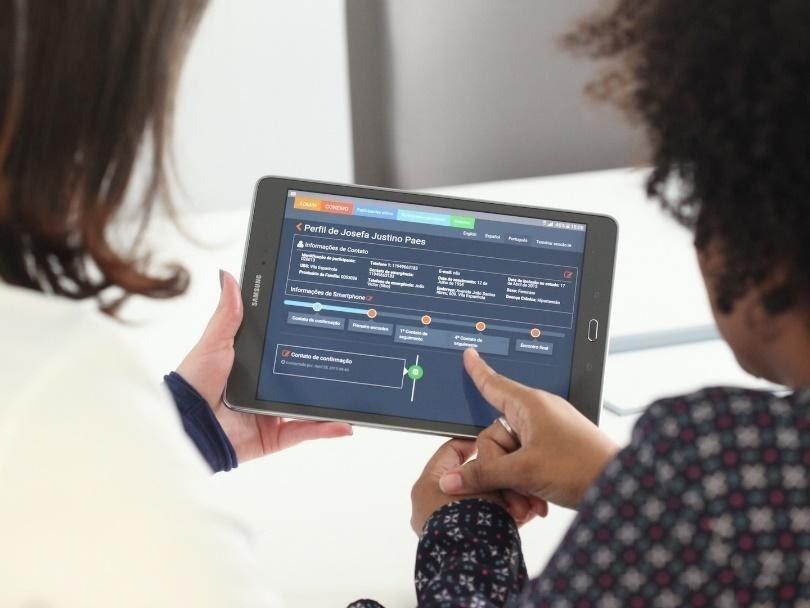 Supervisora clínica preparando auxiliar de enfermagem para uso do tablet para acompanhamento de seus participantes