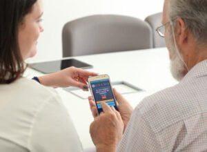 Auxiliar de enfermagem explicando a tecnologia CONEMO para um usuário do SUS