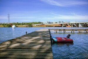 pier de madeira em lago e bote vermelho ao lado direito. céu azul com poucas nuvens ao fundo