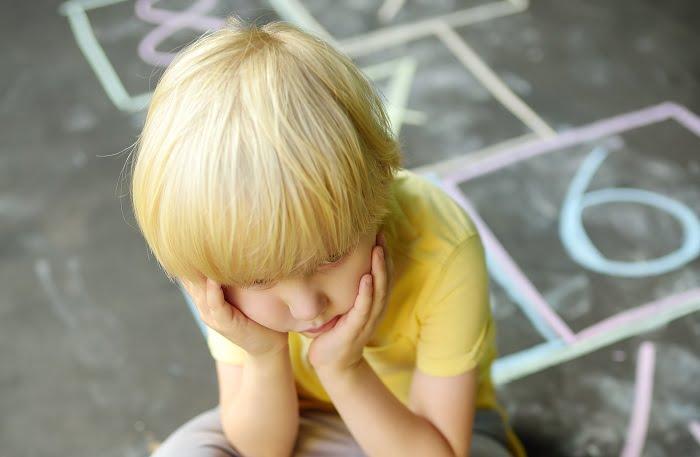 garoto loiro sentado no chão