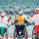 O brasileiro Wallace dos Santos (c) posa para foto no pódio com medalha de ouro do arremesso de peso pela classe F55 nos Jogos de Tóquio